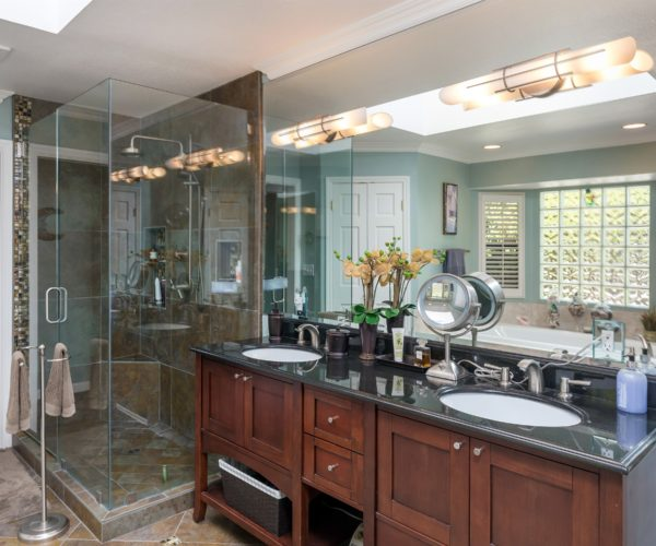 Master bath features twin sinks and separate bath and shower.